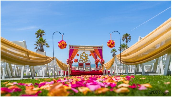 Pink and Purple mandap setup on a beach for an outdoor Hindu wedding ceremony