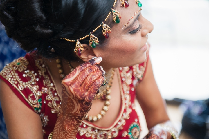 Indian, Jain, Hindu wedding ceremony outdoors in Newport Beach, California. The bride is wearing a red lehenga with matching gold, red, and green jewelry. Putting on her earrings.