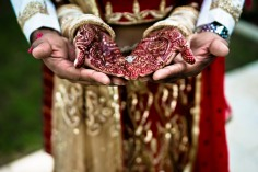 An Indian bride's hands with mehndi with her husband's hands underneath