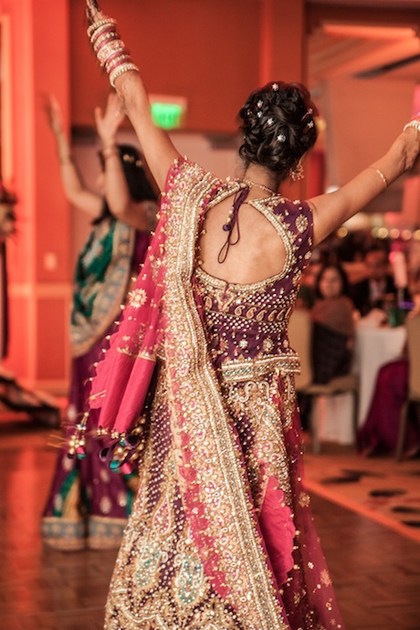 Indian bride dancing at her wedding reception wearing a purple and pink lehenga