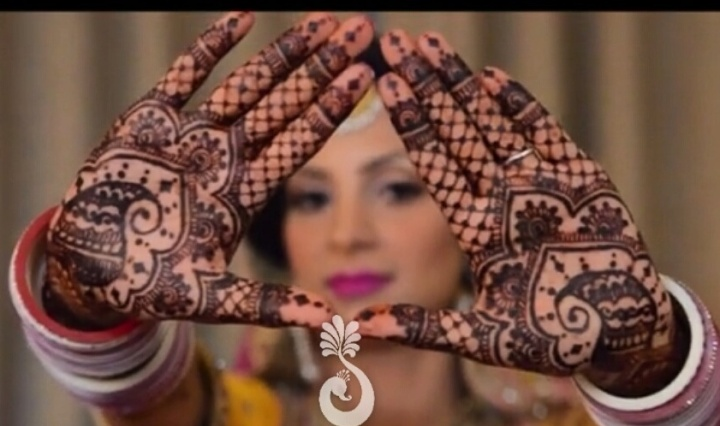An Indian bride holding up her hands in a triangle, showing her mehndi