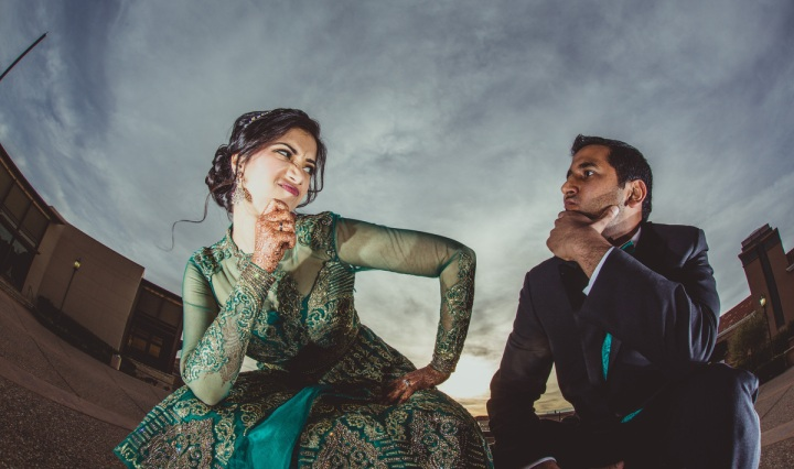 An Indian bride and groom pose for a funny photo at their wedding reception