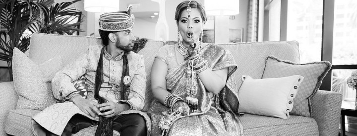 An Indian bride sucking on a lollipop while her groom looks in another direction