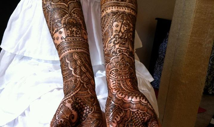 An Indian bride with skinny arms showing off her mehndi that goes all the way to her biceps