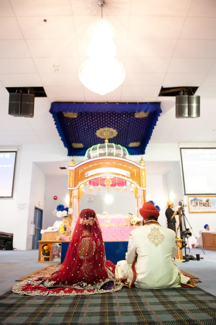 Punjabi Sikh Anand Karaj ceremony with the bride and groom wearing sherwani, pagadi and lehenga