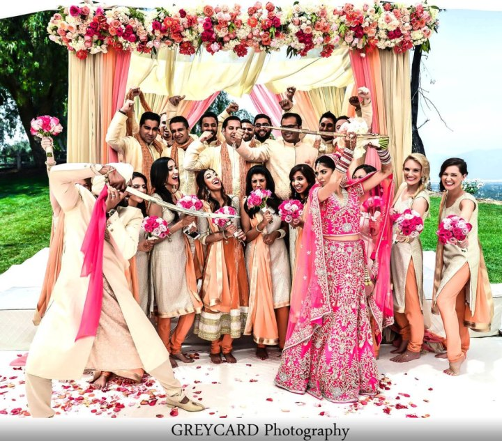 An Indian bride and groom taking a funny wedding photo with their bridal party in the background