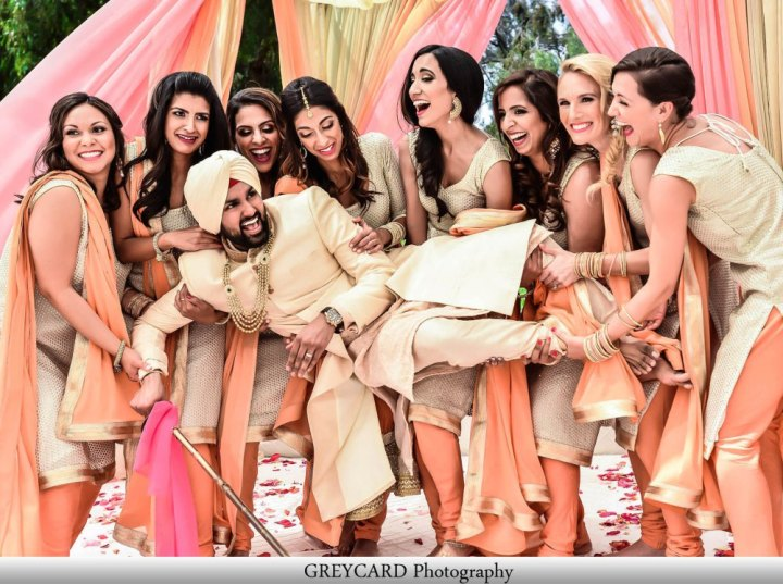 An Indian groom lifted by the bridesmaids for a funny photo.