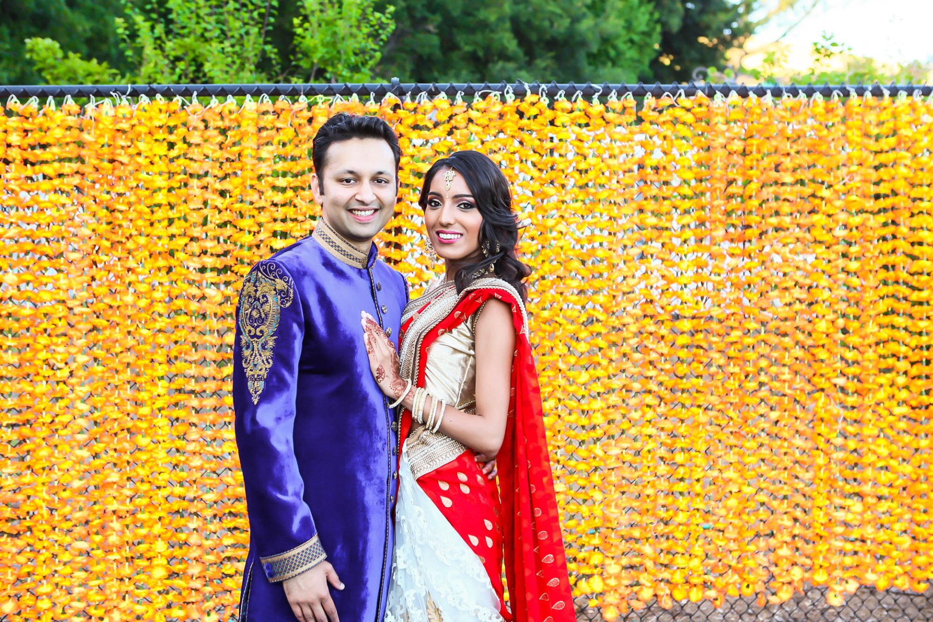 An Indian bride and groom wearing traditional clothes, smiling and posing for the camera
