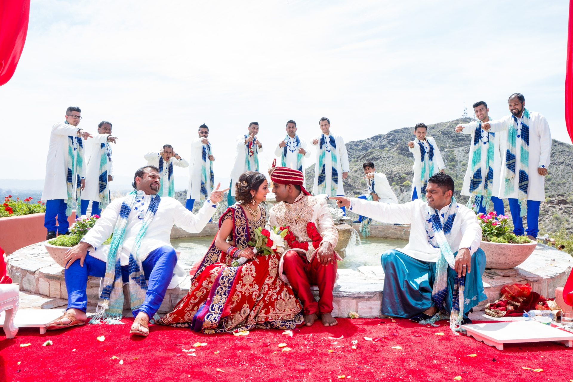 Indian bride and groom taking a funny photo in their mandap, surrounded by the groomsmen