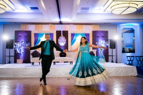 An Indian bride and groom holding hands and dancing at their wedding reception in Newport Beach
