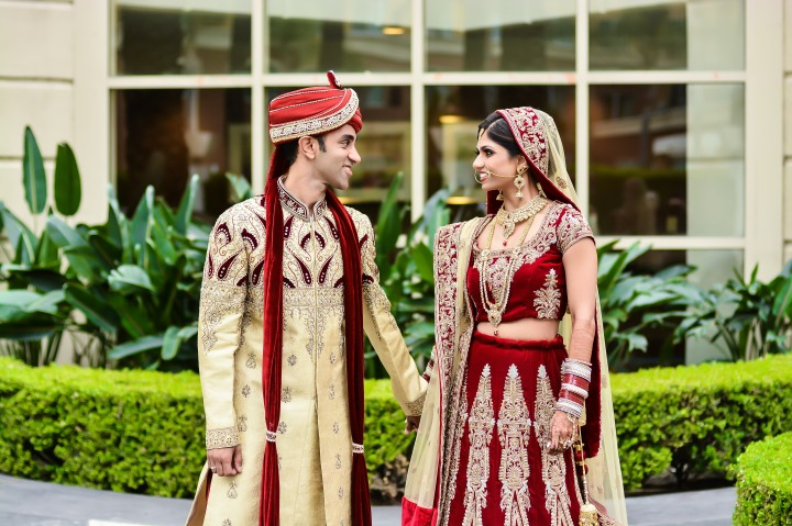 an Indian bride wearing a red lehenga and an Indian groom wearing his sherwani and sehra, looking at each other before their Hindu wedding ceremony.