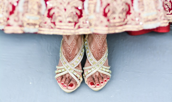 Indian bride's feet showing her high heels, pained toes, mehndi and the bottom of her beautiful lehenga