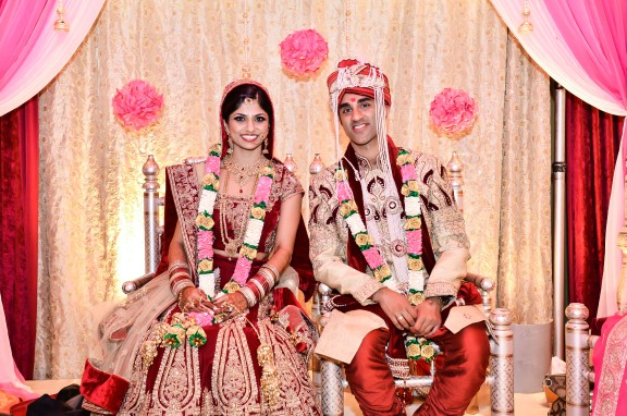 The bride and groom sitting in the mandap. The bride wearing a maroon lehenga and the groom in a matching achkan.