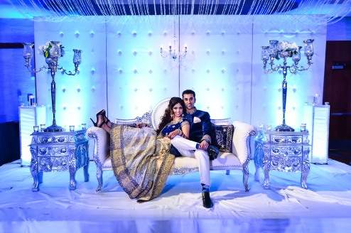 An Indian bride and groom posing for a photo at their sweetheart table at their wedding reception.