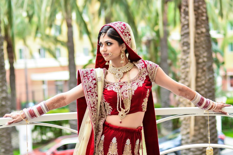 The Indian bride wearing her beautiful red lehenga and gold nath.