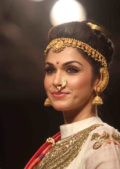 Maharashtrian bride wearing traditional nosering for her wedding. Also wearing headband style tikka and gold jhumkas