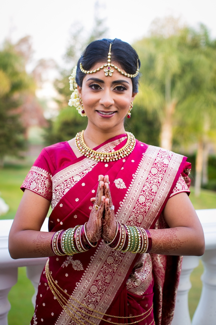 Bride wearing tikka and bindi, gajra and sari for Hindu, smiling, red sari with folded hands for her Indian wedding