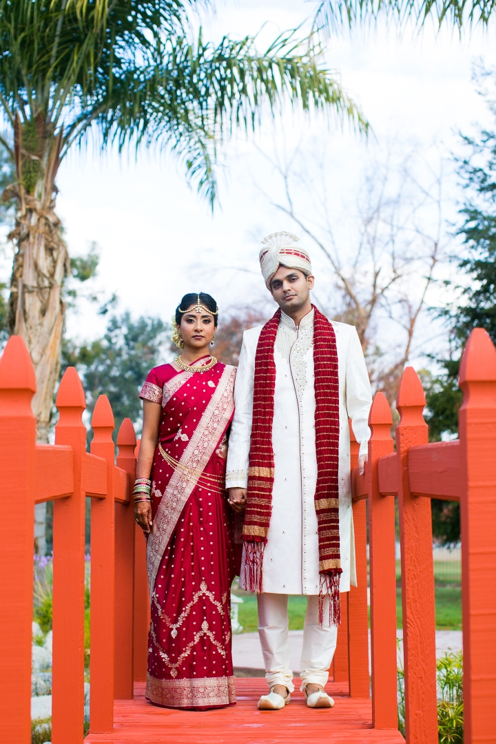 Indian bride and groom at sangeet for an indian wedding wearing sari and sherwani and sera