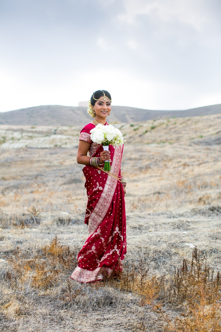 Bride holding flower bouquet and wearing tikka and bindi, gajra and sari for Hindu, smiling, red sari with folded hands for her Indian wedding