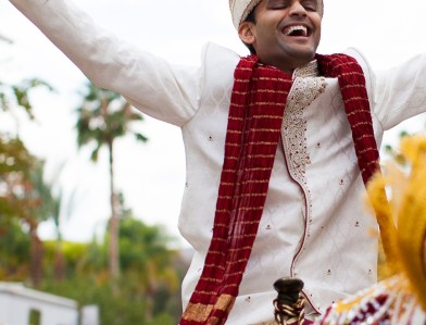 Indian wedding, groom's baraat on a horse wearing a sera and sherwani