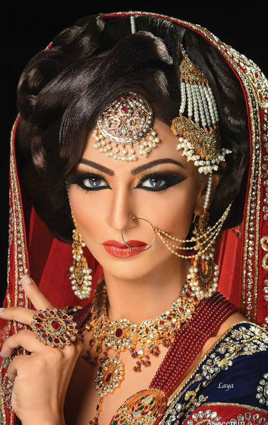 Indian wedding bride wearing a lot of jewelry including nath, tikka, jhoomar, earrings and a nrcklace