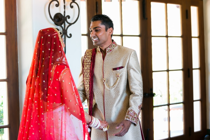 Indian bride and groom wearing their lehenga and sherwani. The groom seeing his bride for the first time ready for their wedding ceremony.