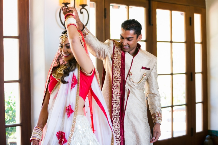 Amish twirling his bride Riddhi before their Indian Hindu wedding ceremony.