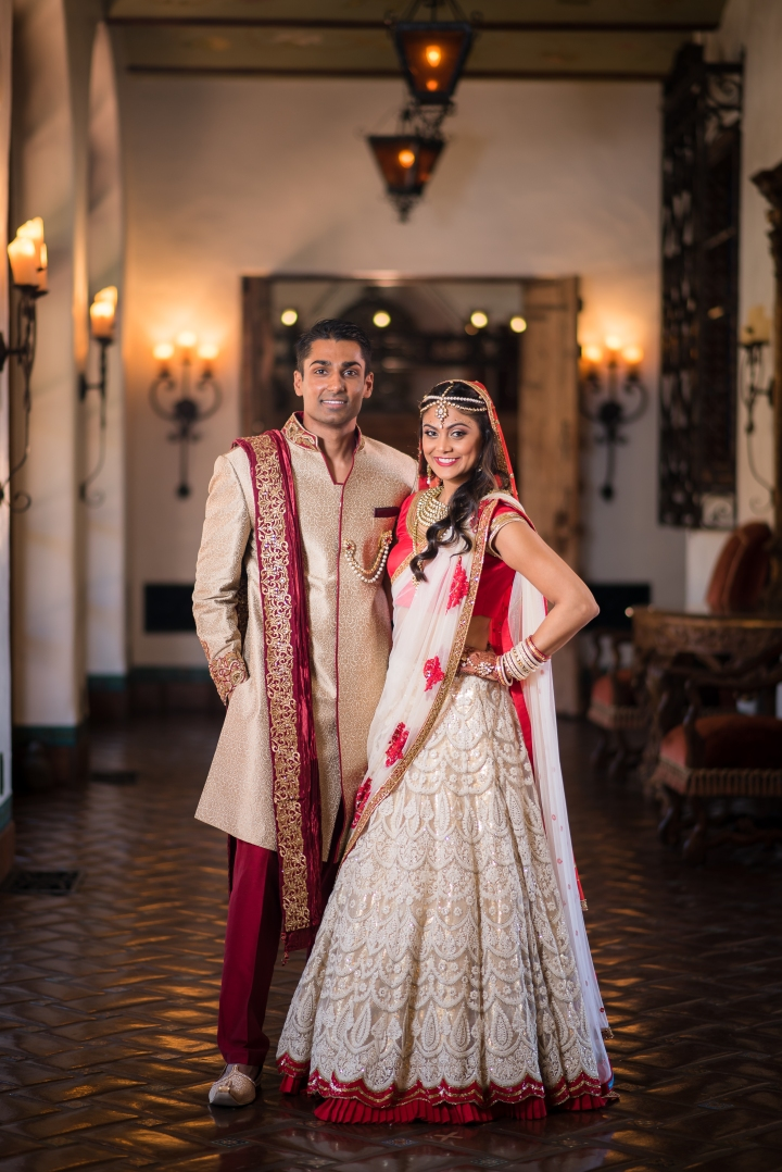The Indian bride and groom wearing their lehenga and sherani before their Gujarati, Indian, Hindu wedding ceremony.