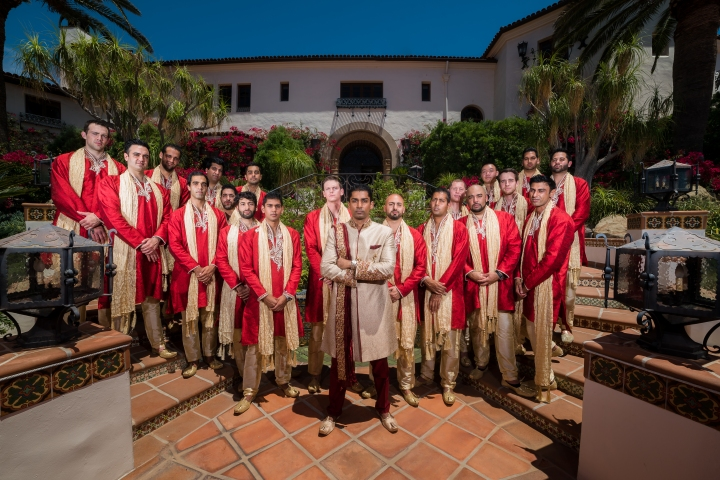 Indian groom posing for a photo with his 19 groomsmen wearing kurtas and dupattas. The groom is wearing a sherwani.