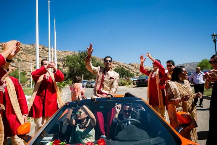 Indian Gujarati groom riding in a McLaren for his wedding baraat.