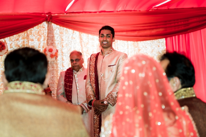 Indian groom wearing his sherwani watching his Indian bride wearing her lehenga, walk towards him for their India, Hindu, wedding ceremony.