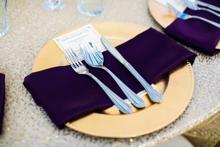 gold charger plates and purple napkins at Indian wedding reception