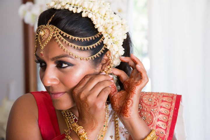 A South Indian bride putting on her jewelry for Indian Hindu wedding