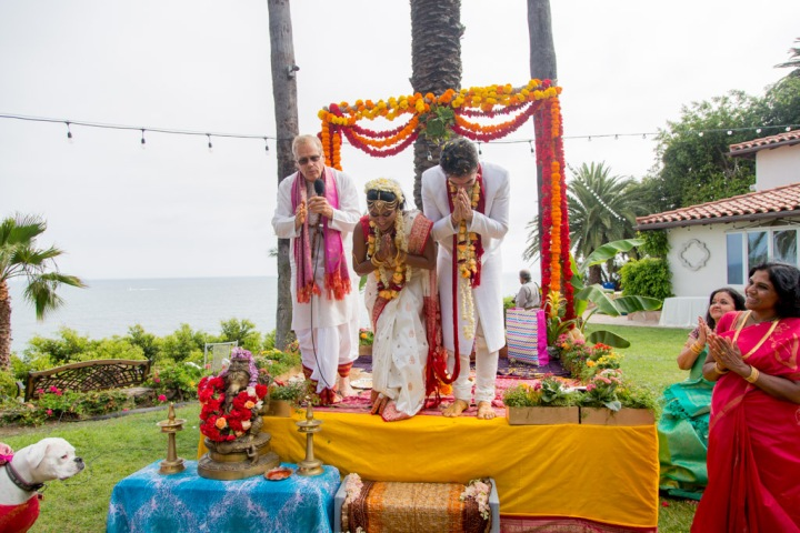 Indian bride and groom bowing in the mandap during their Hindu wedding ceremony.