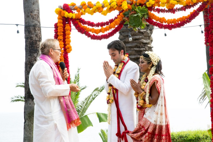 An Indian bride and groom saying a prayer led by their officiant during their Hindu wedding ceremony.