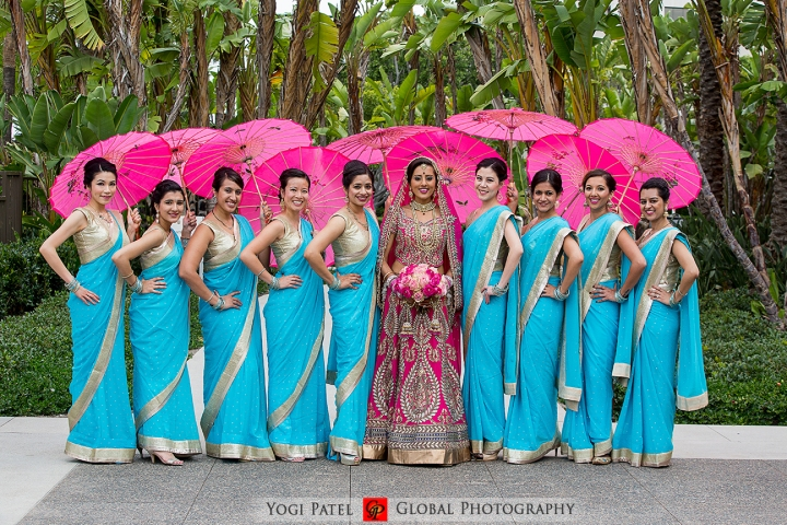 India wedding bridal party. The bride wearing her pink lehenga and the bridesmaids wearing blue saris.