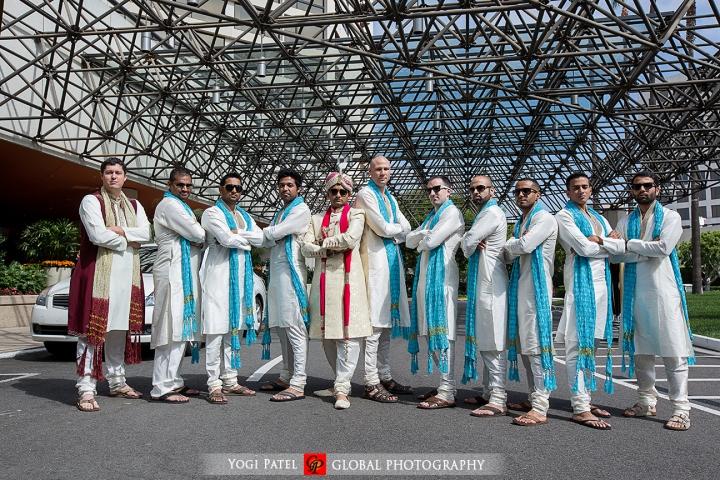 Indian groom wearing sherwani with his groomsmen wearing kurtas and blue dupattas.