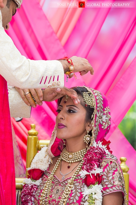 The groom putting sindoor in his wife's maang tiika during the Hindu wedding ceremony.