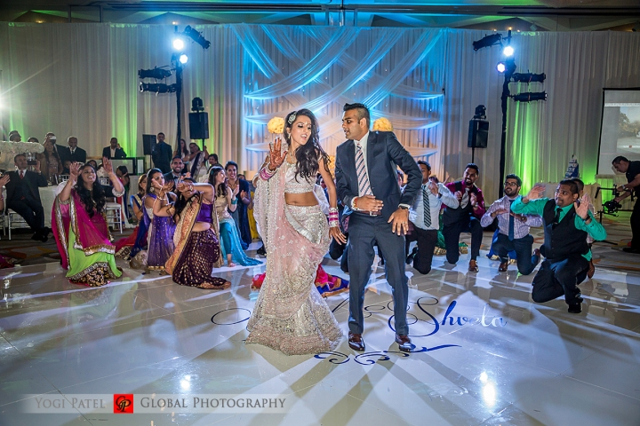 Indian bride and groom wearing their lehenga and suit at their Indian wedding reception.