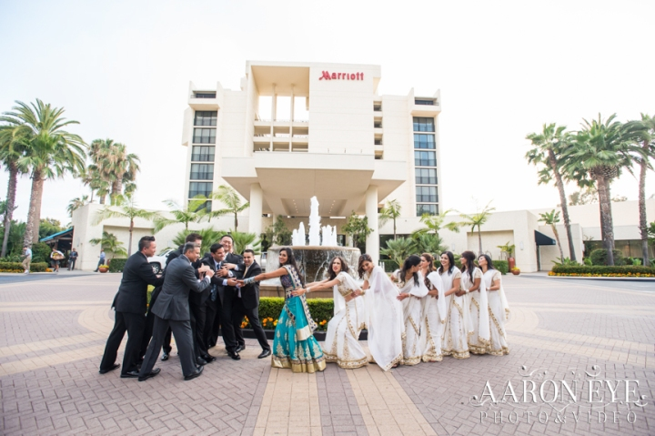 An Indian bride and groom taking a funny photo in front of the water fountain before their wedding reception with their bridal party.