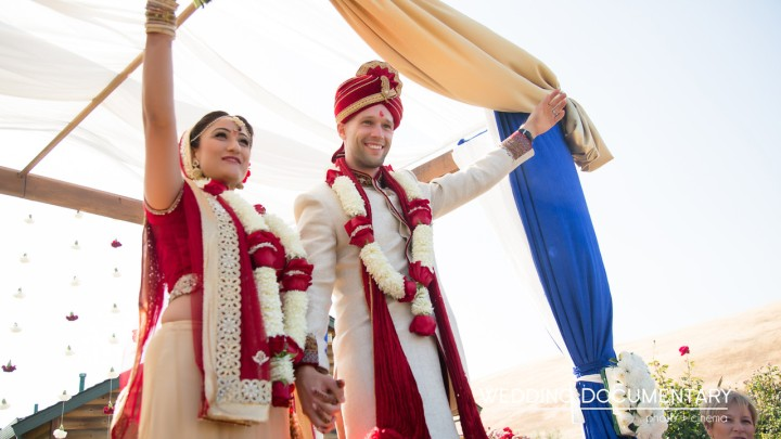 The bride and groom smiling and leaving the mandap after their Hindu wedding ceremony.