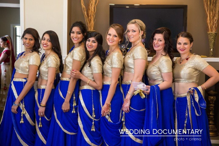 The bridesmaids at an Indian wedding wearing matching blue and gold lehengas