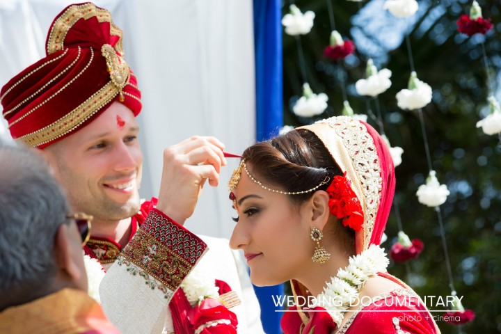 Groom wearing sherwani putting sindoor in bride's maang at Indian Hindu wedding ceremony.