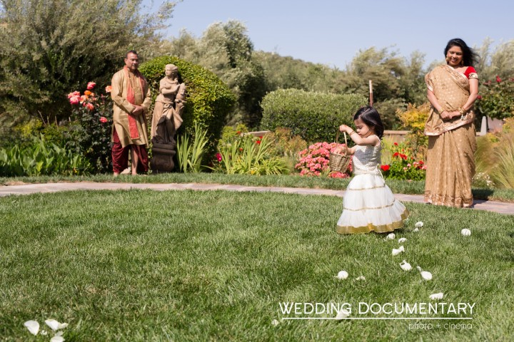 Flower girl showering petals as she enters a wedding ceremony.