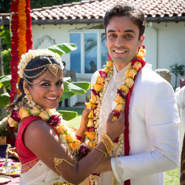 Indian bride and groom posing for a photo after exchanging garlands.