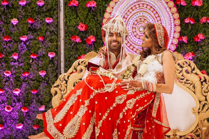 Indian groom carrying his Indian bride after their Hindu wedding ceremony.