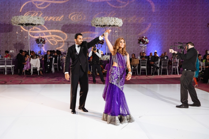 Indian bride wearing purple and silver lehenga on the dance floor at her wedding reception dancing with her husband wearing a black tux and holding her hand in the air.