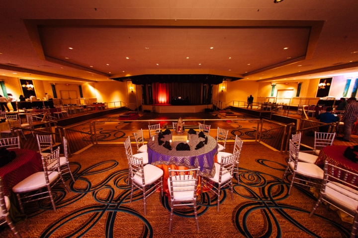 Table and chairs setup for an Indian wedding in a hotel ballroom.