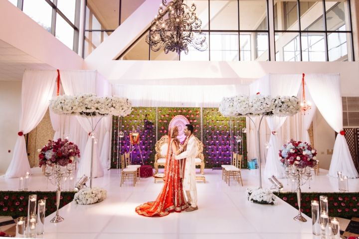 An Indian bride and groom standing in their mandap before their Indian, Hindu, wedding ceremony.