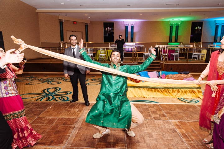 An Indian groom limbo'ing at his wedding sangeet.
